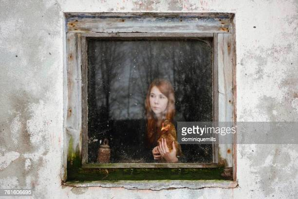 Woman holding a chicken looking through a window