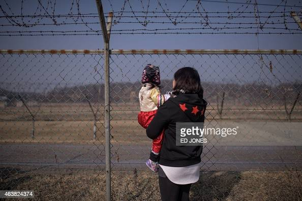 A woman holding a child look towards North Korea as they stand at a military fence at Imjingak park south of the Military Demarcation Line and...