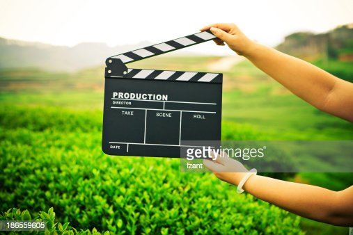 Woman holding a clapper board in front of a field