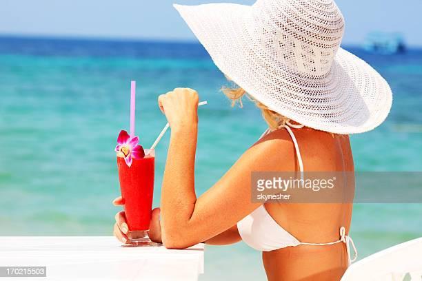 Frau hält einen cocktail.