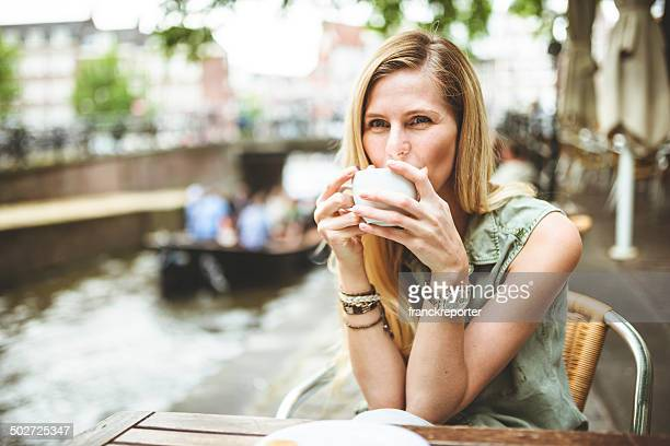 Woman holding a coffee cup in amsterdam