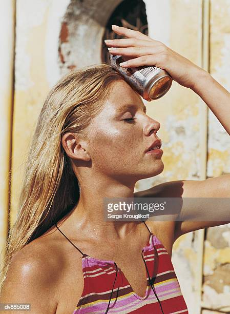 Woman Holding a Cold Can Against her Forehead