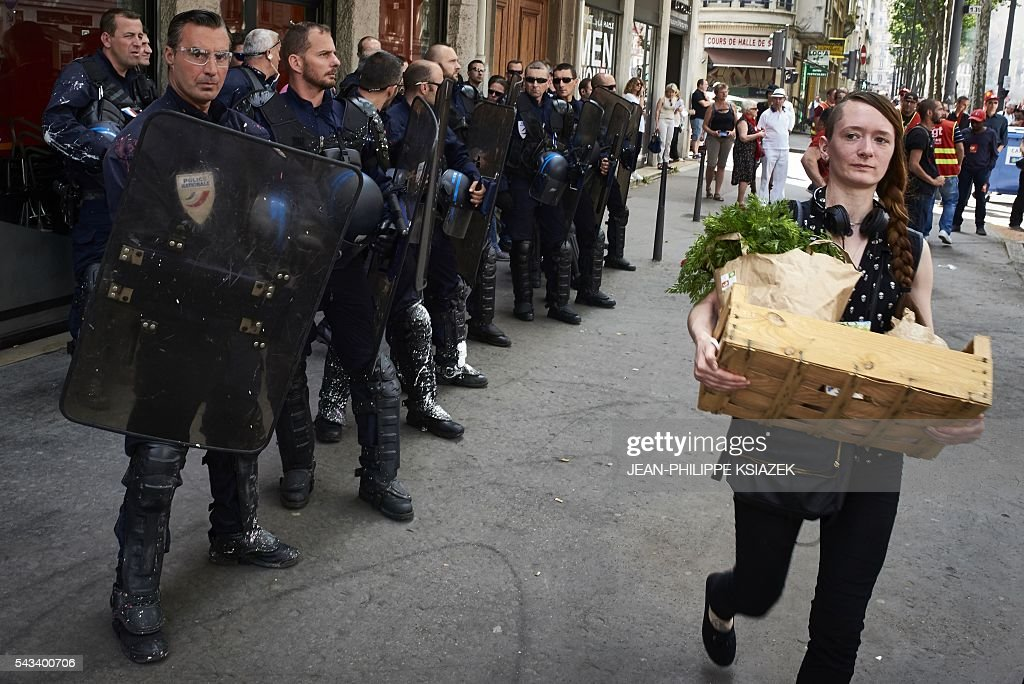 A woman, holding a crate filled with food, walks past French anti-riot police officers patroling during a demonstration against controversial labour reforms, on June 28, 2016 in Lyon. Unions have called repeated strikes and marches in opposition to the law, which seeks to bring down France's intractable 10-percent unemployment rate by making it easier to hire and fire workers. / AFP / JEAN
