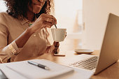 Businesswoman working on laptop computer sitting at home holding a coffee cup in hand. Woman entrepreneur stirring her coffee with spoon while working on laptop.
