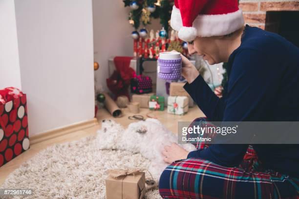 Frau hält eine Tasse Tee vor dem Kamin Weihnachten. Frau entspannt durch warmes Feuer mit einer Tasse heißes Getränk. Winter, Weihnachten Urlaub Konzept