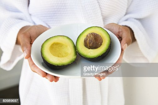 Woman Holding a Cut Avocado : Stock Photo