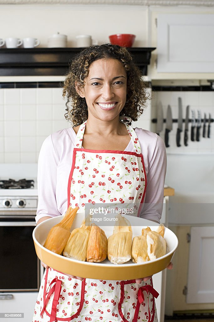 A woman holding a dish of tamales