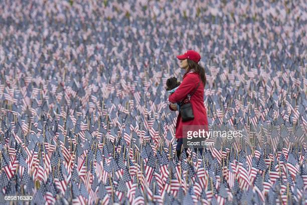 A woman holding a dog walks past the 37252 flags placed on the Boston Common to honor the number of lost Massachusetts military members on May 29...