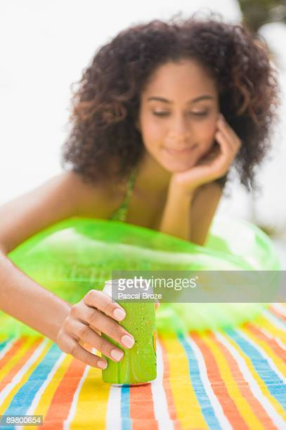Woman holding a drink can and sunbathing at the poolside