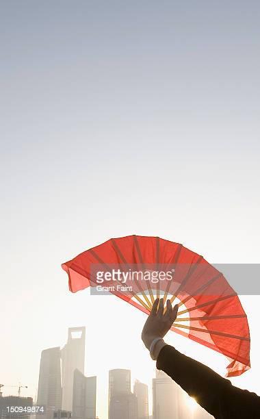 Woman holding a fan against the Shanghai skyline