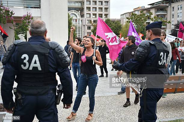 A woman holding a flag of a French trade union shouts and gestures in front of Policemen during a protest against the Labour law reform organised by...