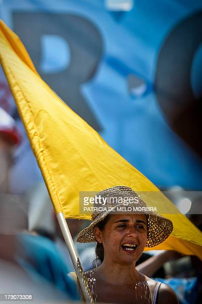 A woman holding a flag shouts slogans as she protests with hundreds of workers gathered near the Belem Palace during a general public workers...