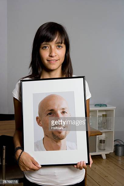 A woman holding a framed photograph