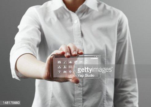 Woman holding a futuristic smartphone : Bildbanksbilder