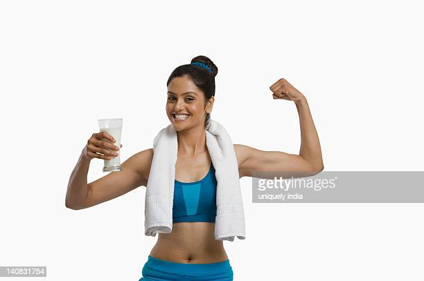 Woman holding a glass of milk and flexing her biceps