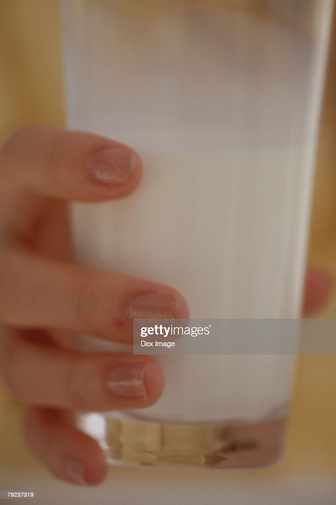 Woman holding a glass of milk : Stock Photo