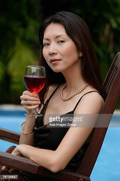 Woman holding a glass of wine, swimming pool in the background, portrait