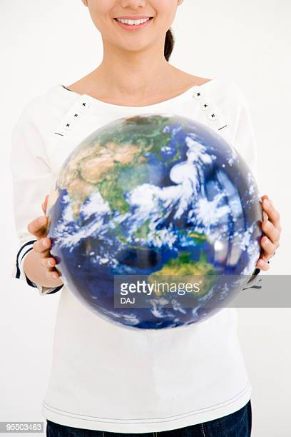 Woman holding a globe, smiling, white background