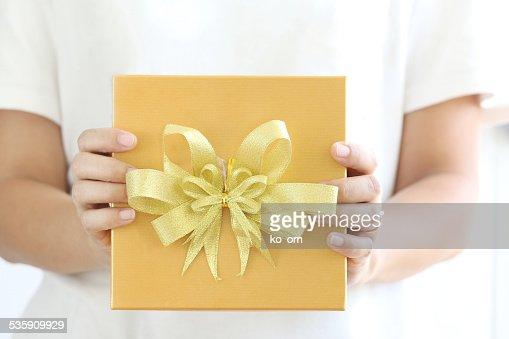 Mujer agarrando la caja de regalo oro. : Foto de stock