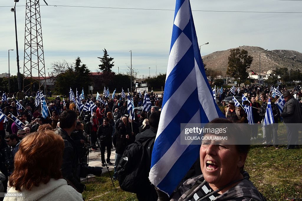A woman holding a Greek flag shouts towards the pro-migrant protesters , while participating in a rally against the construction of a new transit camp for refugees and migrants , near the port of Piraeus in Athens area on February 8, 2016. Dozens of Greek riot police have been deployed for rally organized by the far right Golden Dawn party against plans to build a new transit camp as pro-migrants groups staged a counter-demonstration near the site. / AFP / LOUISA GOULIAMAKI