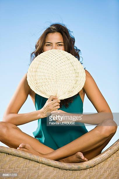 Woman holding a hand fan in front of her mouth