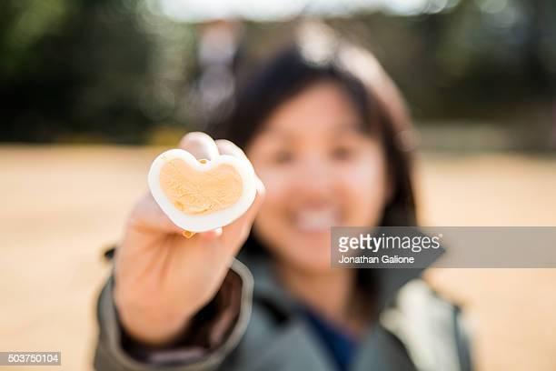 Woman holding a heart shaped egg with chopsticks