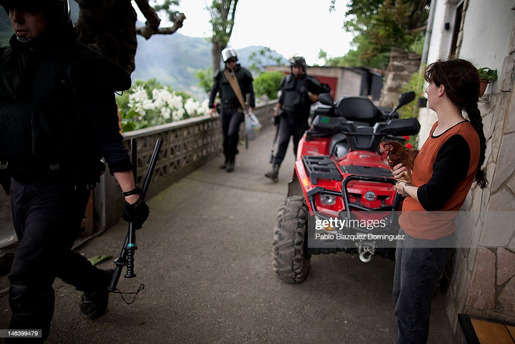A woman holding a hen watches riot police walking in Figaredo near Mieres after their search for miners on June 15, 2012 in northern Spain. Spanish coal miners are staging a nationwide strike organised by unions opposed to subsidy reductions from 300 million to 110 million Euros.