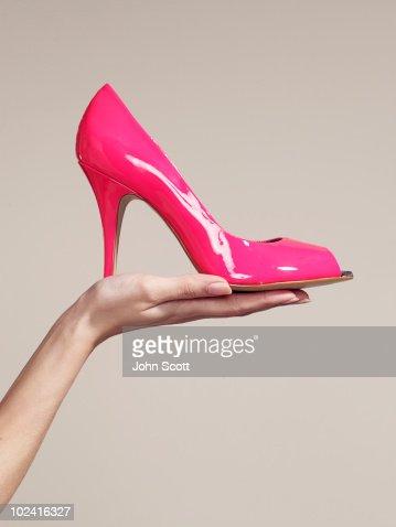 Woman holding a high heel shoe : Stock Photo