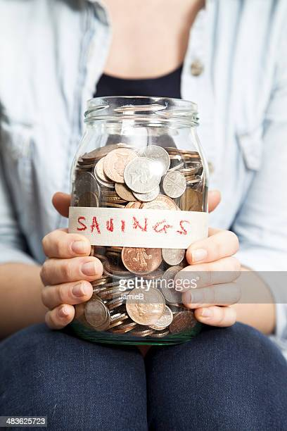 Woman holding a jar with coins