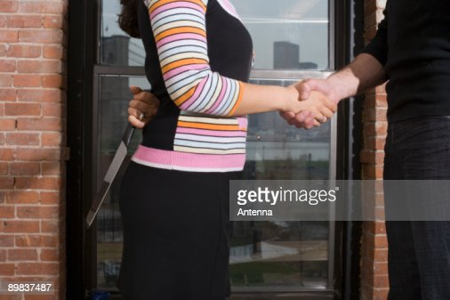 A woman holding a knife behind her back whilst shaking hands