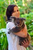 Young beautiful woman holding a Koala in Queensland, Australia