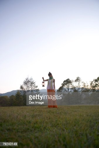 Woman holding a lamp in a park : Stock Photo