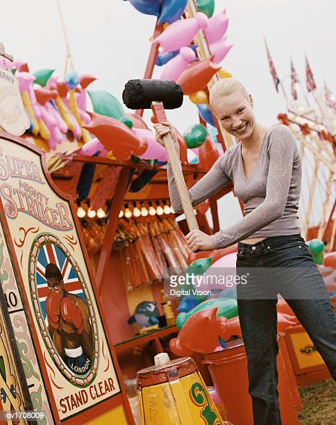 Woman Holding a Large Mallet, Ready to Play an Old Fashioned Strength Game, at a Fairground
