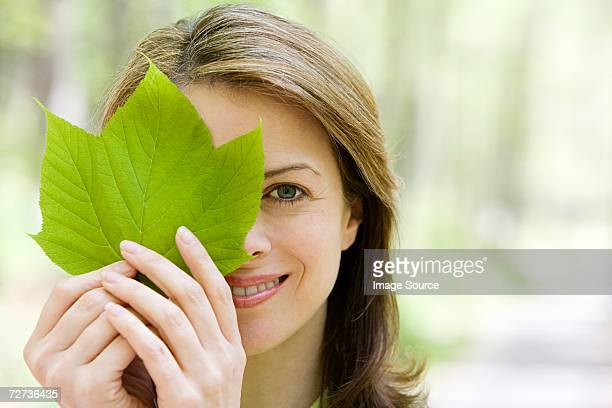 Woman holding a leaf to her eye