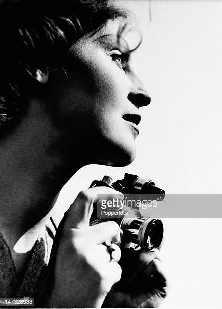A woman holding a Leica 35mm compact camera circa 1955