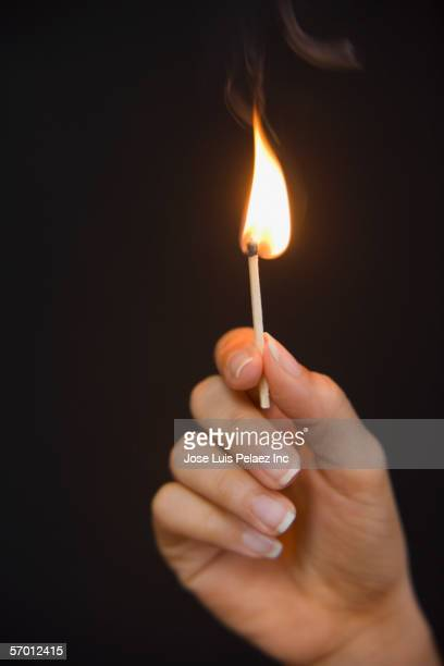 Woman holding a lit match