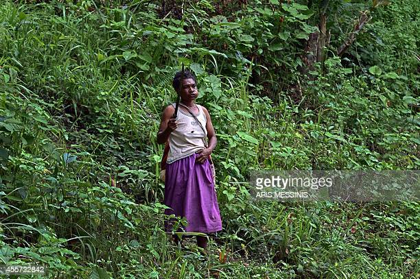 A woman holding a machete stands in the jungle near the town of Malalaua Papua New Guinea on September 4 2014 AFP PHOTO / ARIS MESSINIS