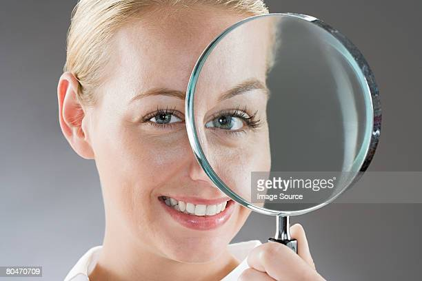 A woman holding a magnifying glass