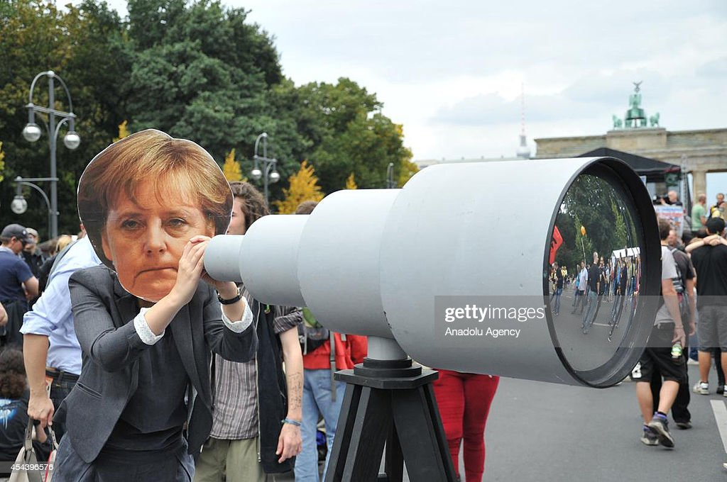 A woman holding a mock telescope and wearing a mask showing German Chancellor Merkel attends the demonstration 'Liberty instead of Fear' in front of Brandenburg Gate in the capital Berlin, Germany on August 30, 2014.