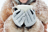 Woman holding a mug to get warm in winter