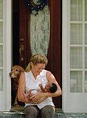 Woman holding a newborn baby on her doorstep