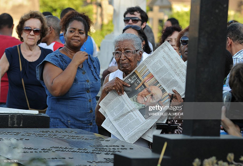 A woman holding a newspaper with a picture of Brazilian architect Oscar Niemeyer attends the funeral of he at the Sao Joao Batista cemetery in Rio de Janeiro, Brazil on December 7, 2012. Niemeyer, the Brazilian icon who revolutionized modern architecture and designed much of the country's futuristic capital Brasilia, died in Rio de Janeiro Wednesday at 104.