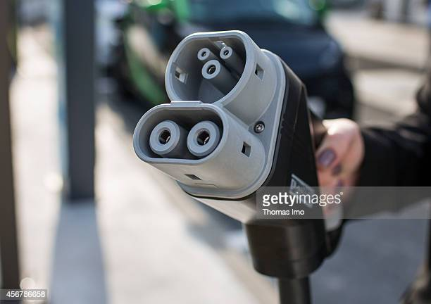 Woman holding a nozzle to charge electric vehicles at a multienergy filling station of the oil company Total on September 29 in Berlin Germany Photo...