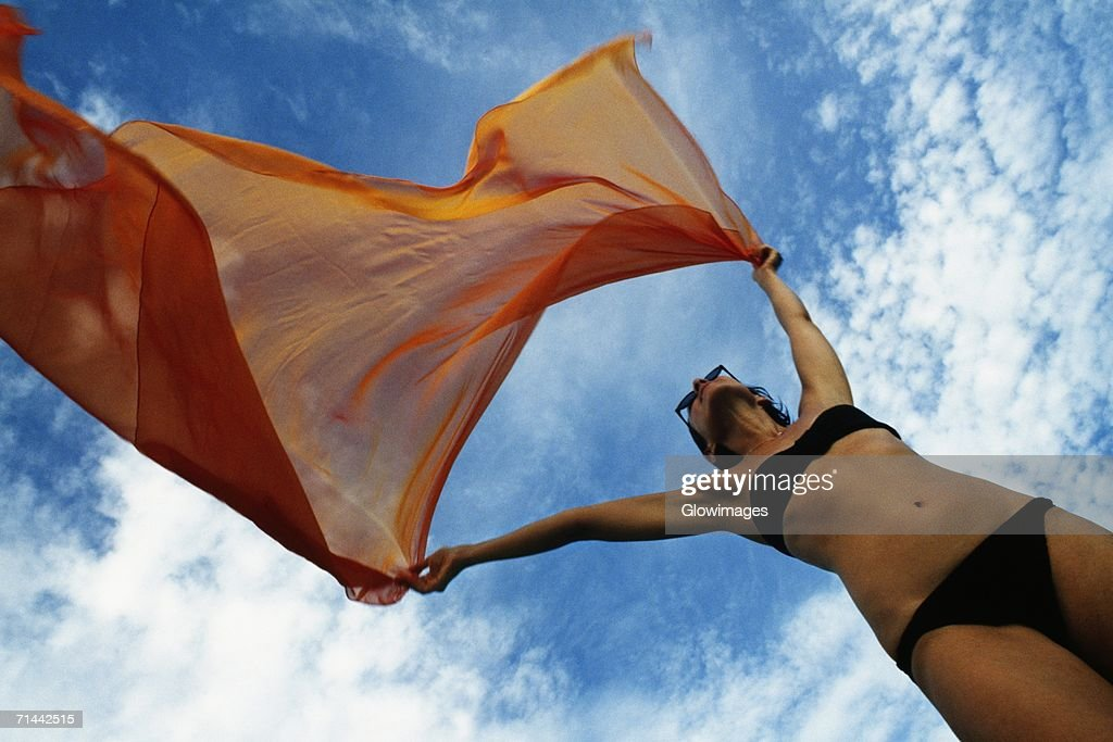 Woman holding a orange colored fabric in the tropical breeze on the island of Barbados, Caribbean : Stock Photo