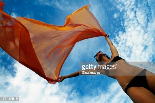Woman holding a orange colored fabric in the tropical breeze on the island of Barbados, Caribbean