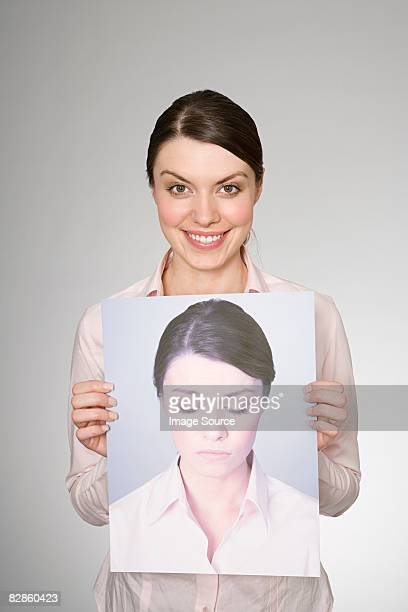 A woman holding a photograph of herself looking sad