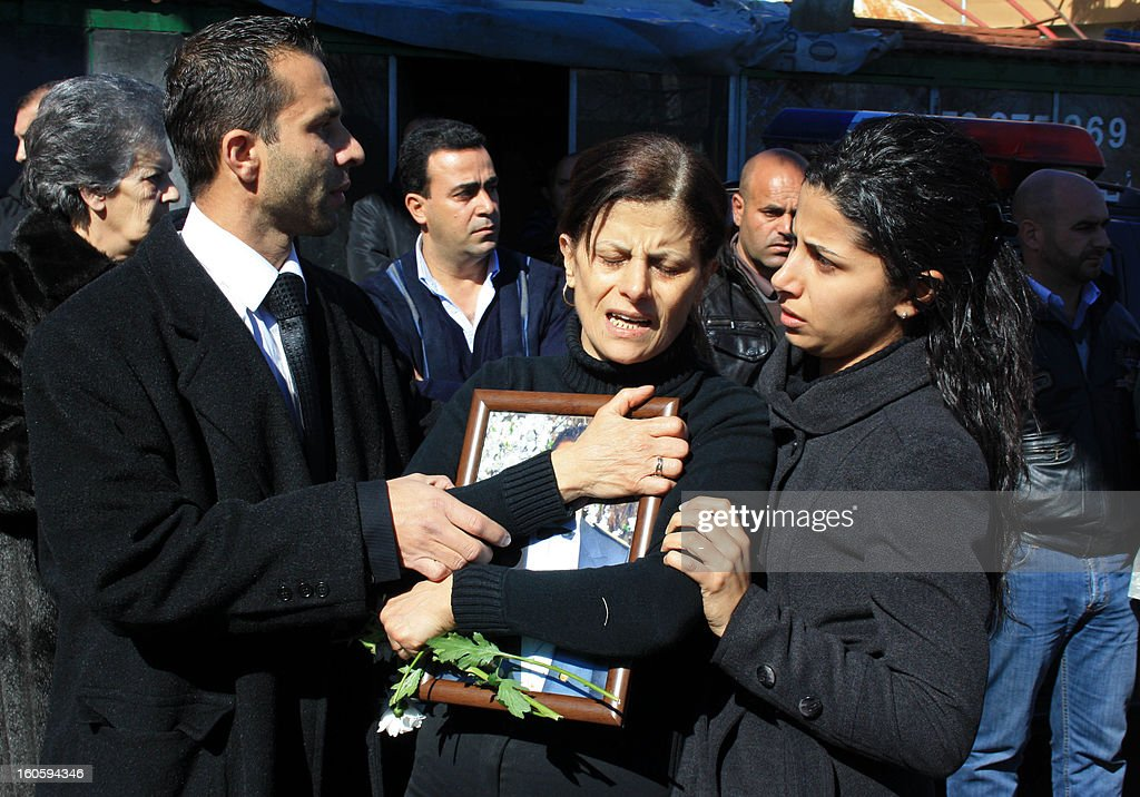 A woman, holding a picture of Lebanese army captain Pierre Bashalana, one of the two soldiers who were killed in a clash with unidentified gunmen in Arsal, a village near the border with Syria, is comforted during his funeral procession in the city of Mraijat, on the outskirts of Beirut, on February 3, 2013. Bashalana was killed alongside sergeant Ibrahim Zahrman while several others were wounded in the clash with an unspecified number of gunmen, who also sustained casualties on February 1.
