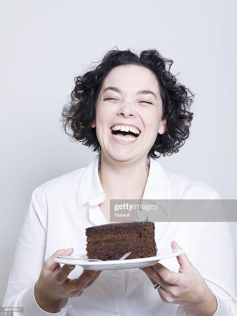 woman holding a plate of cake : Stock Photo