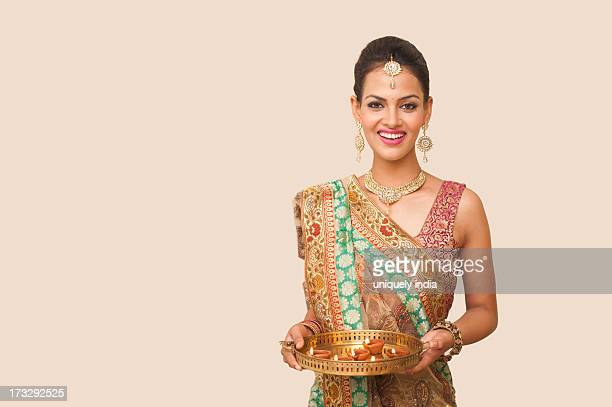 Woman holding a plate of oil lamps on Diwali