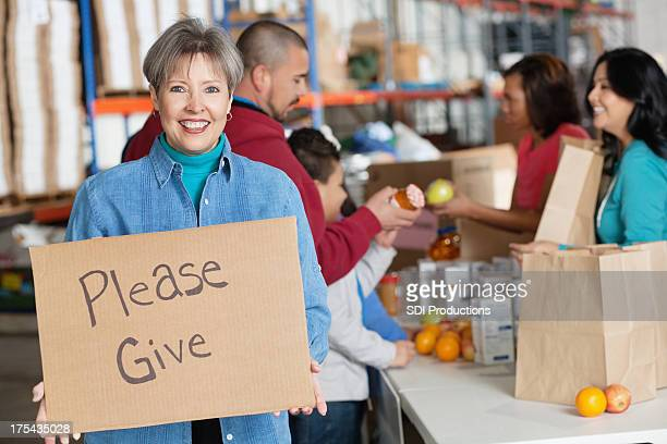 Woman holding a please give sign at donation center